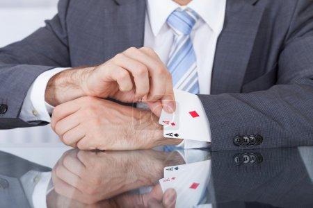 Photo pour Gros plan d'un homme d'affaires tirant un as caché de la manche - image libre de droit