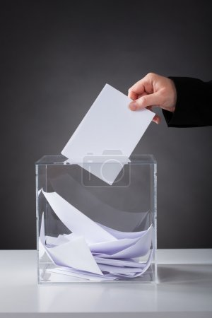 Close-up Of Hand Putting Ballot In Glass Box...