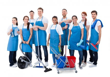 Photo for Large diverse group of janitors wearing blue aprons standing grouped together with their equipment smiling at the camera  isolated on white - Royalty Free Image