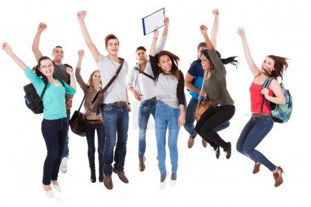 Photo pour Portrait de pleine longueur des étudiants de l'Université réussie avec les bras levés en sautant sur fond blanc - image libre de droit
