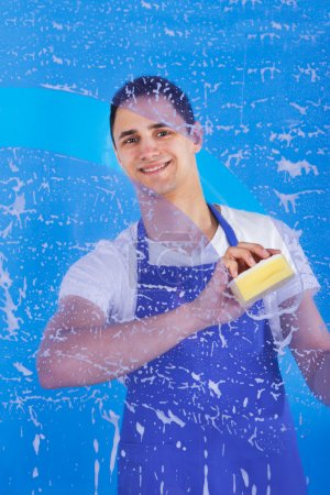 Photo for Portrait of young male servant cleaning glass with sponge over blue background - Royalty Free Image