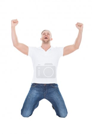 Photo pour Heureux homme acclamations en liesse tomber sur ses genoux avec ses poings soulevés en l'air alors qu'il célèbre un succès sur blanc - image libre de droit