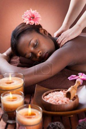 Photo pour Vue latérale de la jeune femme à recevoir le massage d'épaule au salon spa - image libre de droit