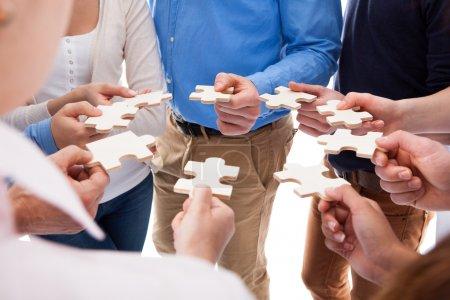 Photo pour Vue grand angle des personnes connectant des pièces de puzzle sur fond blanc - image libre de droit