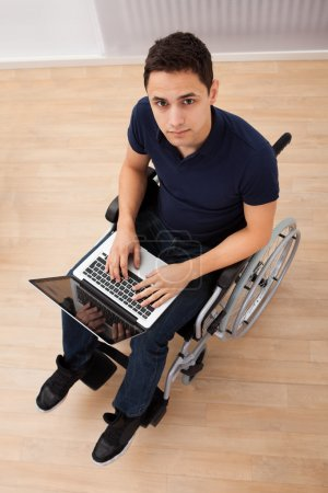 Handicapped Man Using Laptop On Wheelchair