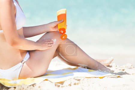 Woman In Bikini Applying Sunscreen At Seashore