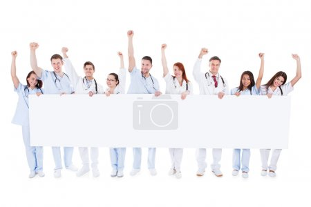 Photo pour Grand groupe diversifié du personnel médical permanent en ligne tenant une bannière blanche blanche avec le fond et les acclamations élever leurs poings en l'air isolé sur blanc - image libre de droit