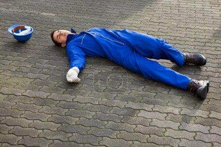 Foto de Longitud total de joven inconsciente reparador en uniforme tirado en la calle - Imagen libre de derechos