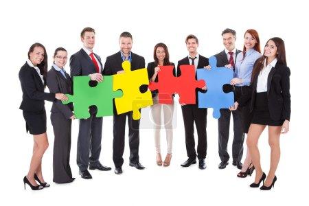Photo pour Groupe d'hommes d'affaires tenant quatre grandes pièces de puzzle de couleur vive conceptuel du travail d'équipe dans la résolution d'un problème d'affaires ou de relever un défi isolé sur blanc - image libre de droit