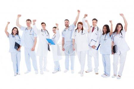Photo pour Grande équipe médicale multiethnique diverse commandes acclamations et poinçonnage de l'air avec leurs poings qu'ils célèbrent un succès ou motivent eux-mêmes isolé sur blanc - image libre de droit