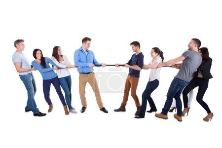 Photo pour Deux équipes adverses ayant un remorqueur de guerre tirant sur les extrémités opposées d'une corde dans une démonstration de force conceptuelle de défi de la concurrence et de détermination sur blanc - image libre de droit