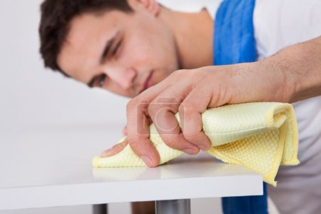 Photo for Handsome young man cleaning table with napkin at home - Royalty Free Image