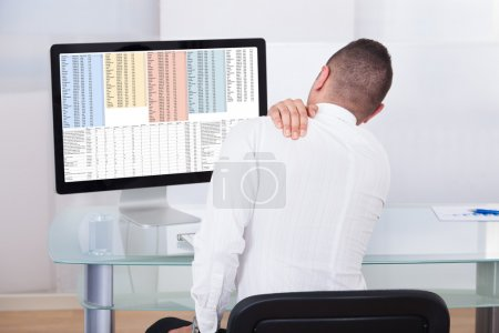 Businessman With Shoulder Pain Using Computer