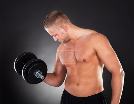 Muscular man lifting weights in a gym