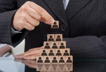 Photo pour Midsection of businesswoman stacking wooden team blocks at table - image libre de droit