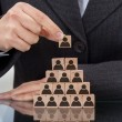 Midsection of businesswoman stacking wooden team b...