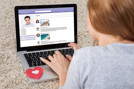 Photo pour Vue arrière de la femme bavarder sur les sites de réseautage social en utilisant un ordinateur portable - image libre de droit