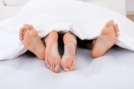 Low Section Of Intimate Couple Under Blanket