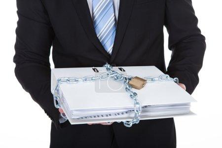 Photo pour Homme d'affaires tenant un fichier confidentiel top secret enfermé avec une chaîne et un cadenas pour empêcher un accès non autorisé isolé sur blanc - image libre de droit