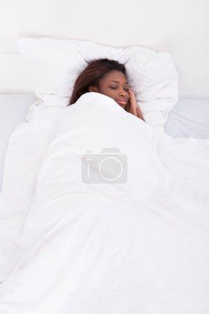 Photo pour Souriante femme afro-américaine, dormir dans son lit - image libre de droit