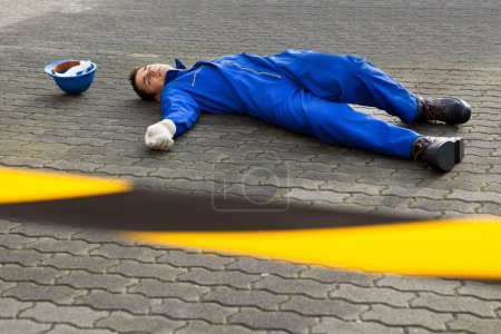 Photo for Full length of young unconscious technician lying on street - Royalty Free Image