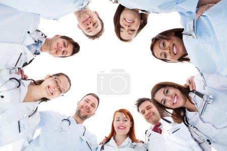 Photo pour Grande équipe médicale multiethnique diverse commandes groupées en cercle tous vers le bas en regardant la caméra et souriant isolé sur blanc avec fond central - image libre de droit