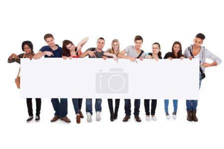 Photo pour Portrait de pleine longueur de collégiens multiethnique confiant affichant le panneau d'affichage blanc sur fond blanc - image libre de droit