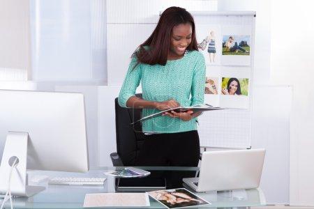 Happy African American female photo editor working...