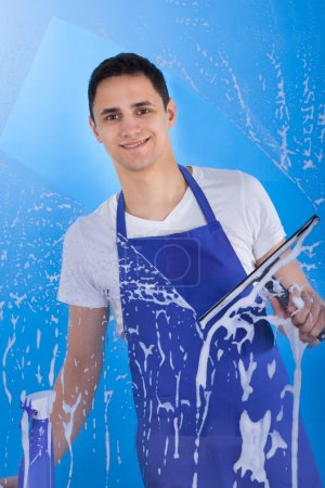 Photo for Portrait of young male servant cleaning glass with squeegee over blue background - Royalty Free Image