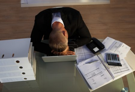 Exhausted businessman sleeping an a stack of files...