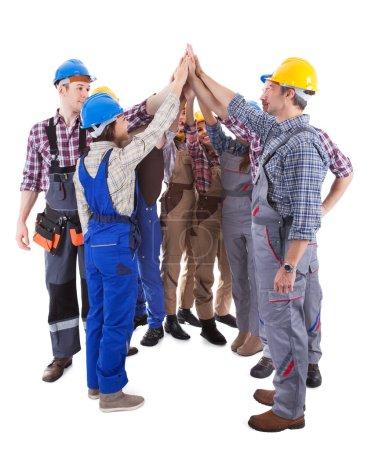 Photo pour Groupe multiethnique d'artisans donnant un geste cinq élevé tels qu'ils sont dans un cercle indiquant leur engagement et la motivation pour un projet d'équipe isolé sur blanc - image libre de droit