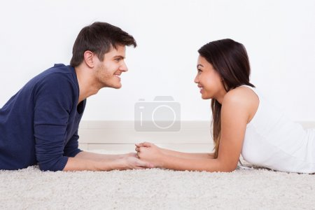 Loving Young Couple Lying On Rug