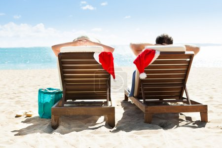 Photo for Rear view of couple with Santa hats relaxing on deck chairs at beach resort - Royalty Free Image
