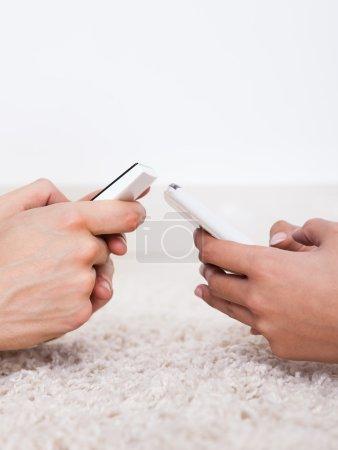Hands Text Messaging Through Smartphones On Rug