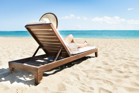 Photo for Side view of young woman in bikini sunbathing on deck chair at beach - Royalty Free Image