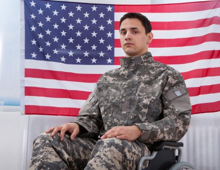 Patriotic Soldier Sitting On Wheel Chair Against American Flag
