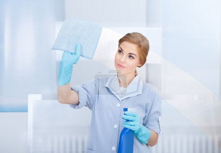 Photo for Portrait Of Happy Young Maid Cleaning Glass With Sponge - Royalty Free Image