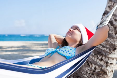 Photo pour Jeune femme réfléchie portant le chapeau de Père Noël dans l'hamac à la plage - image libre de droit