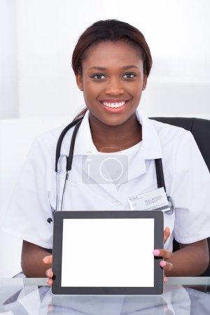 Female Doctor Holding Blank Digital Tablet At Desk