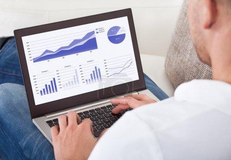 Photo pour Sur la vue de l'épaule de l'écran d'un homme d'affaires, analyse des graphiques sur son ordinateur portable - image libre de droit