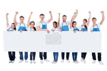 Photo pour Grand groupe multiethnique diversifiée de nettoyeurs de porter des tabliers applaudir comme ils détiennent une bannière blanche long blanche avec fond pour votre texte ou la publicité isolé sur blanc - image libre de droit