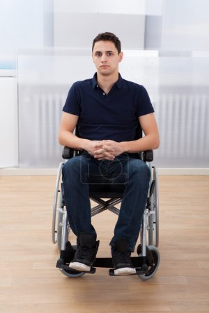 Handicapped Man Sitting On Wheelchair At Home