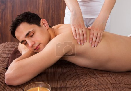 relaxed man receiving shoulder massage in