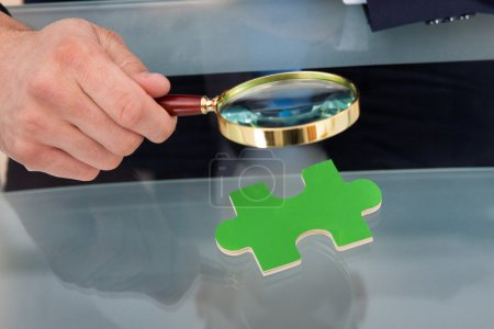 Businessman Scrutinizing Puzzle Piece With Magnifying Glass