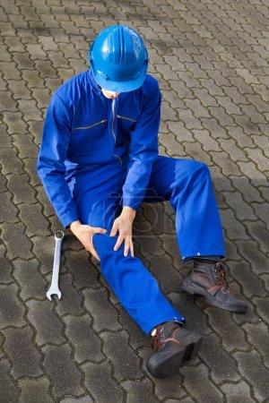 Foto de Longitud total de técnico sufre de dolor en la rodilla mientras está sentado en la calle - Imagen libre de derechos