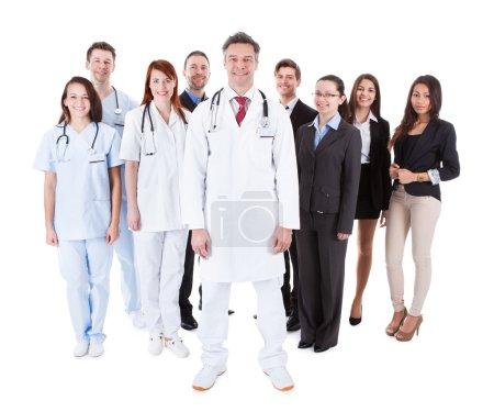 Photo pour Docteur debout devant son équipe. Isolé sur blanc - image libre de droit