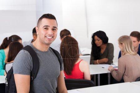 Photo pour Portrait d'étudiant mâle confiant transport sac à dos avec ses camarades de classe en arrière-plan - image libre de droit