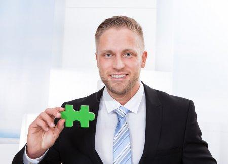 Photo pour Homme d'affaires réussi tenant une pièce de puzzle vert comme il indique qu'il a résolu un problème venir avec une idée inspirante ou surmonter un fond texturé blanc défi - image libre de droit