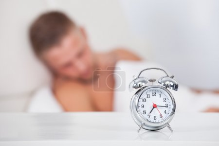 Photo for Alarm clock about to ring in the morning showing a quarter past seven with a man sleeping in bed in the background  focus to the clock - Royalty Free Image