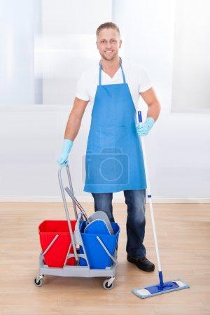 Photo pour Concierge, nettoyage parquet avec une serpillière et un panier avec deux seaux pour le désinfectant et l'eau s'arrêter de sourire à la caméra, qui se rend à son travail dans un immeuble de bureaux - image libre de droit